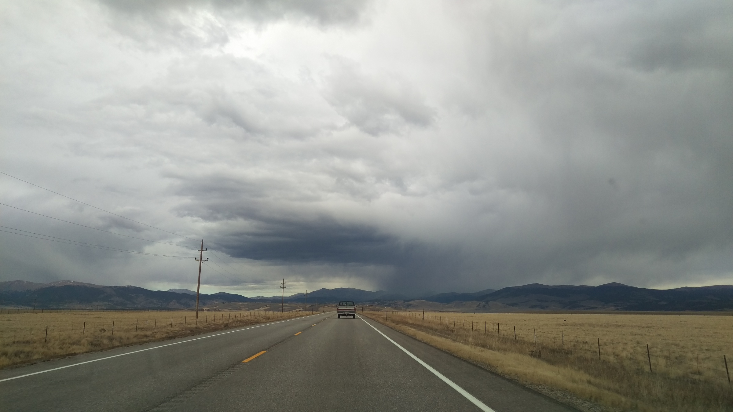 A wide, cloudy landscape reveals a paved road and a pickup truck in the distance.