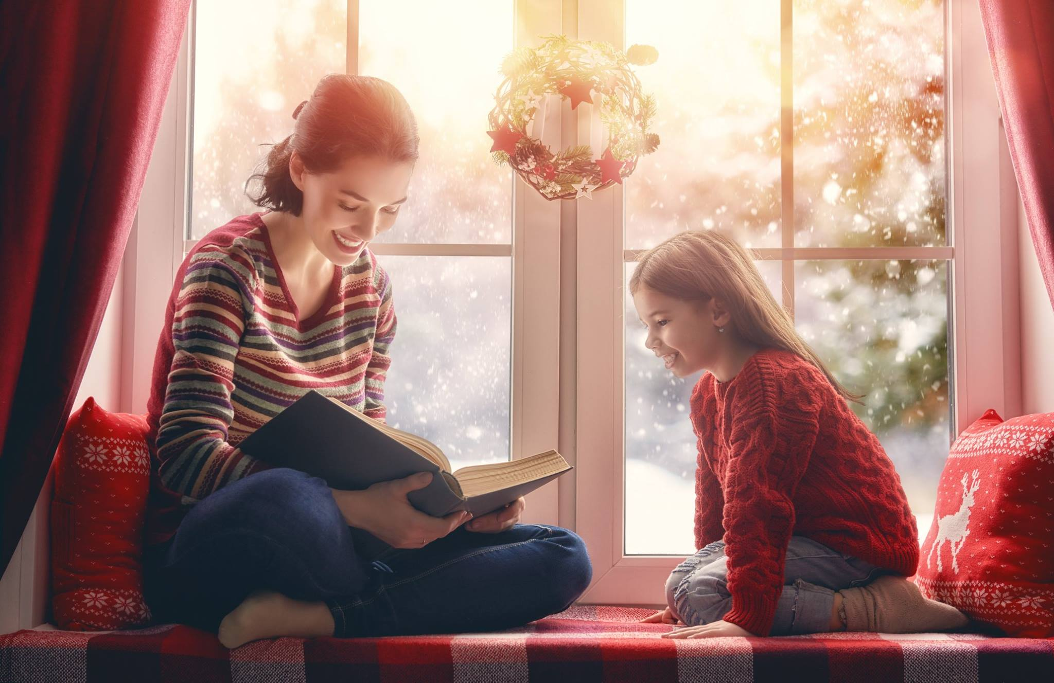 A woman reads to a child in a christmas scene.