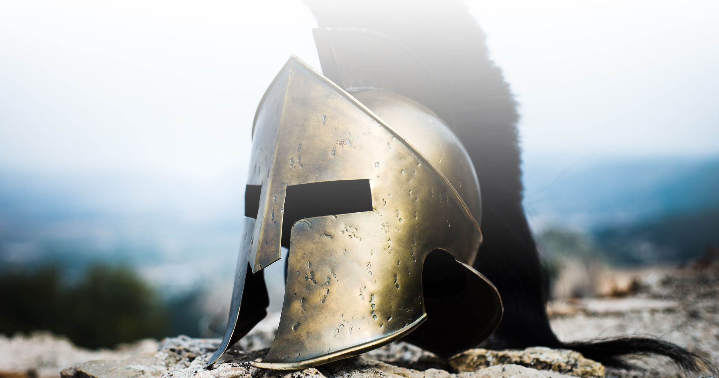 A Spartan helmet rests on rocks with a blurry background.